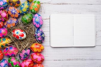 Superficie de madera con huevos de pascua y cuaderno en blanco