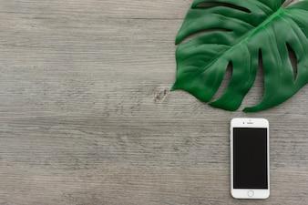 Superficie de madera con teléfono móvil y hoja verde
