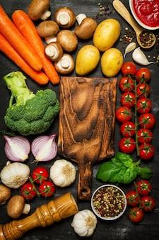 Superficie negra con verduras y una tabla de cortar