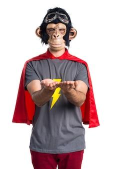 Superhéroe mono hombre sosteniendo algo