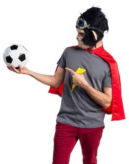 Superhéroe mono hombre sosteniendo un balón de fútbol