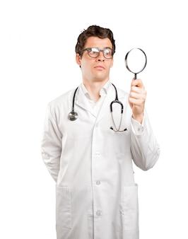 Surpreendido médico usando una lupa contra el fondo blanco