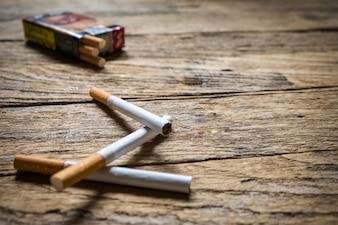 Tabaco en el cigarrillo, tumbado en una mesa de madera.