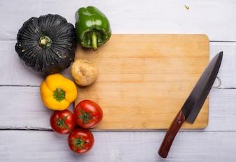 Tabla de picar con verduras y un cuchillo