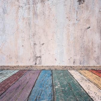 Tablas de madera de colores estropeadas y una pared estropeada de cemento