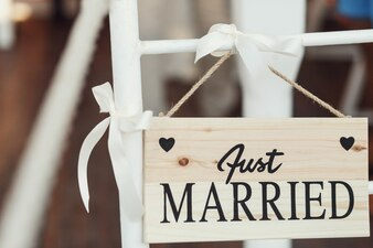 "Tablero de madera con letras ""Just married"" se cuelga en silla blanca"