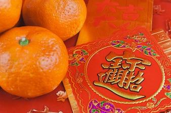 Tarjeta roja y dorada con una mandarina para celebrar el año chino nuevo
