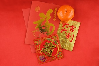 Tarjeta roja y dorada junto a una naranja