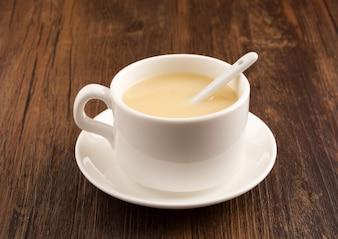 Taza blanca de café sobre mesa de madera