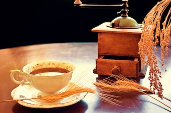 Taza de café con un molinillo antiguo