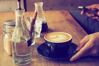Taza de café con una botella de agua y un vaso con palos de canela sobre una mesa de madera