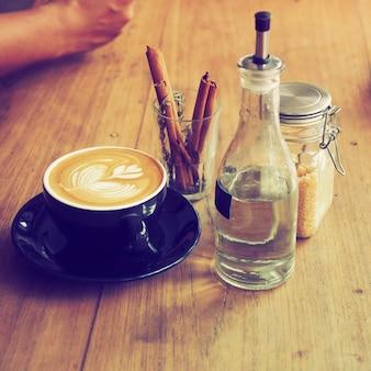 Taza de café con una botella de agua y un vaso con palos de canela