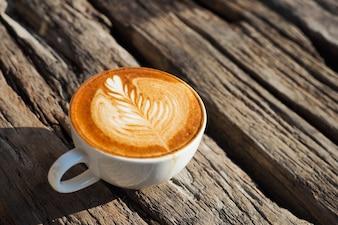 Taza de café con una espiga de trigo dibujada en espuma
