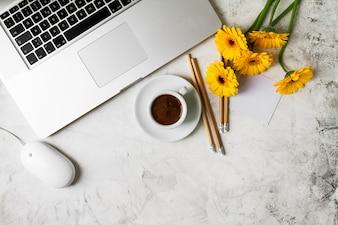 Taza de café con unas flores amarillas y un portatil