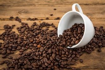 Taza de café tumbada con granos de café saliendo de ella