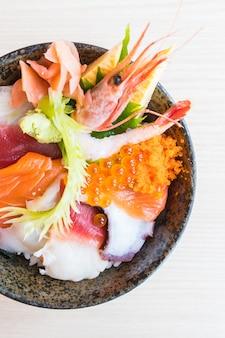 Tazón de arroz japonés con mariscos sashimi en la parte superior