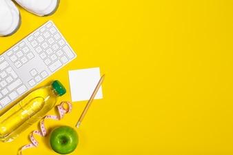 Teclado de ordenador con fruta y una botella de agua