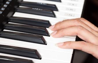 Teclado de piano con una mujer
