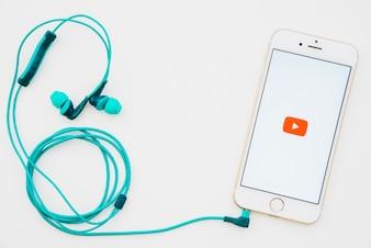Teléfon con la aplicación de youtube y auriculares