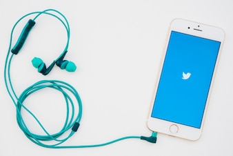 Teléfono con la aplicación de twitter y auriculares