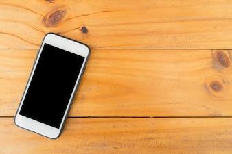 Teléfono móvil con pantalla en blanco sobre fondo de madera de mesa. Vista superior con espacio de copia.