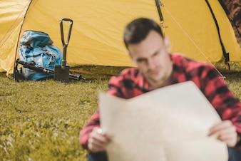 Tienda de campaña y mochila con viajero borroso