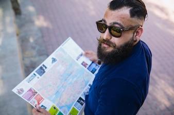 Tío atractivo posando con un mapa