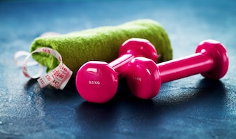 Toalla verde, con una cinta métrica y unas pesas rosas