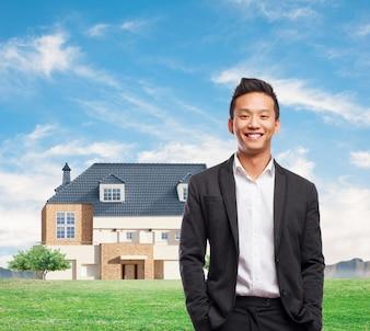 Trabajador alegre con casa moderna de fondo