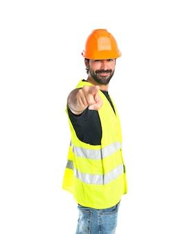 Trabajador que señala a la parte delantera sobre fondo blanco