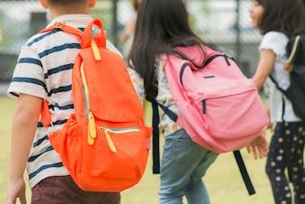 Tres alumnos de la escuela primaria van de la mano. Muchacho y muchacha con los bolsos de escuela detrás de la parte posterior. Comienzo de las clases. Día cálido de otoño. De vuelta a la escuela. Pequeños estudiantes de primer grado.