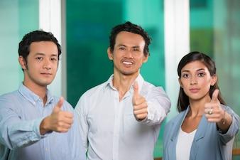 Tres contenido gente de negocios que muestra los pulgares para arriba