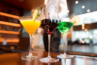 Tres vasos de diferentes bebidas alcohólicas en la barra