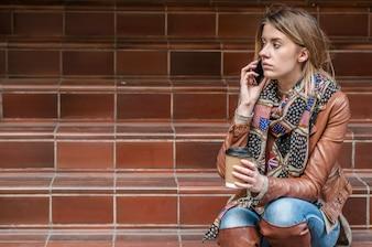 Tristes noticias. La mujer joven trastornada con el teléfono móvil lee el mensaje.