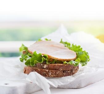 Trozo de carne circular encima de lechuga y pan