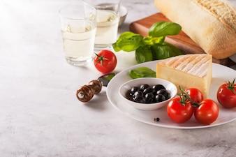 Trozo de queso con tomates y aceitunas negras en un plato