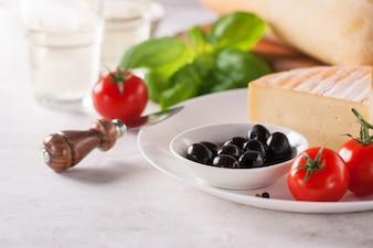 Trozo de queso en un plato con aceitunas y tomates