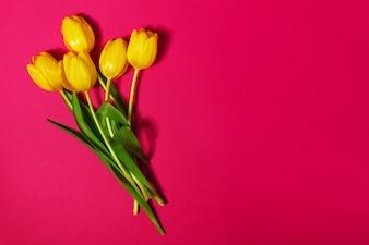 Tulipanes amarillos sobre una mesa roja