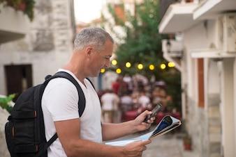Turista mirando el mapa en la calle de la ciudad europea, viajar a Europa. Naranja brillante luz del atardecer, libertad y concepto de estilo de vida activo. Hombre con mochila utilizando y mirando el mapa