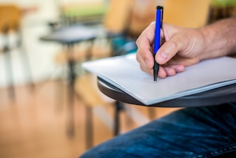 Un hombre está escribiendo / firmando en un papel. Centrado en una mano con la pluma