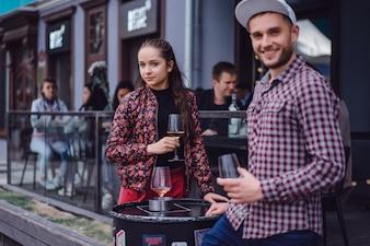 Un hombre y una muchacha están bebiendo el vino en una terraza del verano en un café de la calle. Elegante pareja beber vino en el café