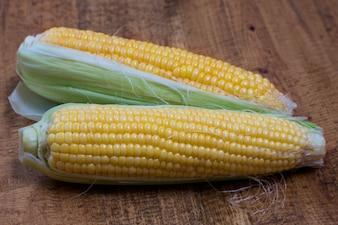Una espiga de maíz aislado en un fondo de madera