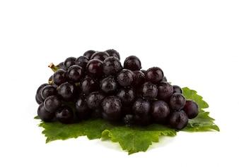 Uva roja con hojas verdes aisladas sobre fondo blanco