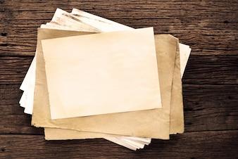 Vaciar el papel viejo sobre la mesa de madera - fondo vintage