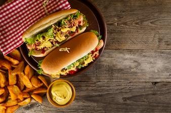 Variedad de clásico estadounidense tradicional sabrosa comida chatarra insalubre sobre fondo de madera con copia espacio. Perritos calientes y patatas fritas.