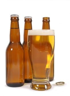 Vaso de cerveza con botellas de color marrón