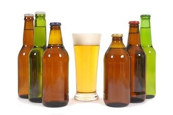 Vaso de cerveza con varias botellas