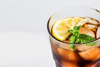 Vaso de cola con limón y hojas aromáticas