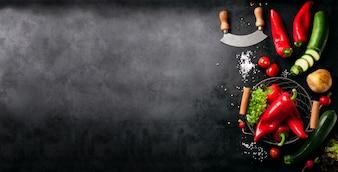 Vegetales y un cuchillo italiano puestos a la izquierda de una mesa negra