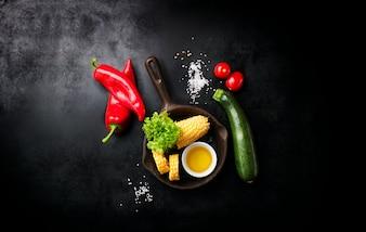 Vegetales y un cuchillo italiano puestos en una mesa negra